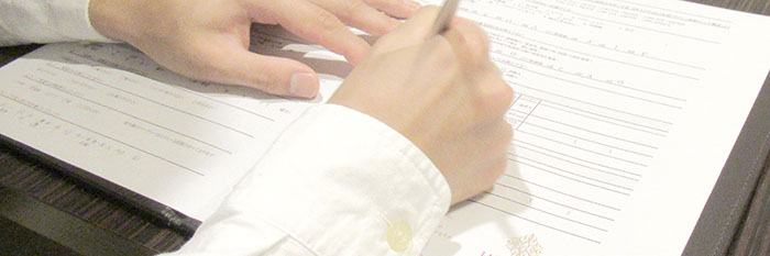 離婚届を書いている男性の手